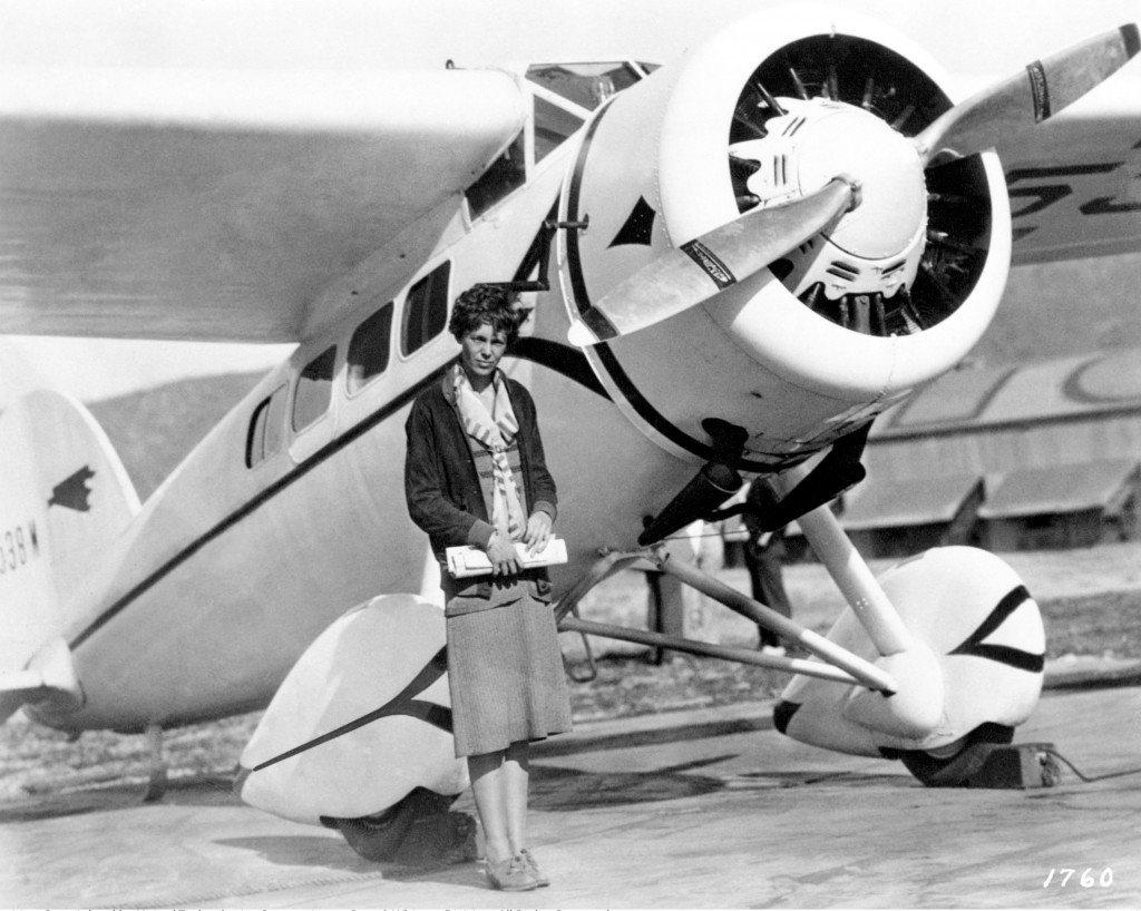 Women in Aviation; Pratt and Whitney. Photograph showing Amelia Earhart standing next to one of the aircrafts that she flew.